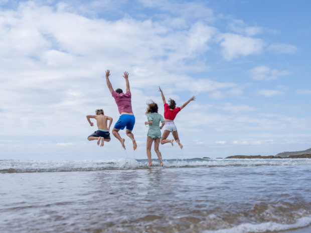 Family jumping over waves at woolacombe beach